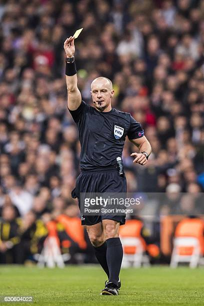 Referee Szymon Marciniak shows the yellow card during the 201617 UEFA Champions League match between Real Madrid and Borussia Dortmund at the...