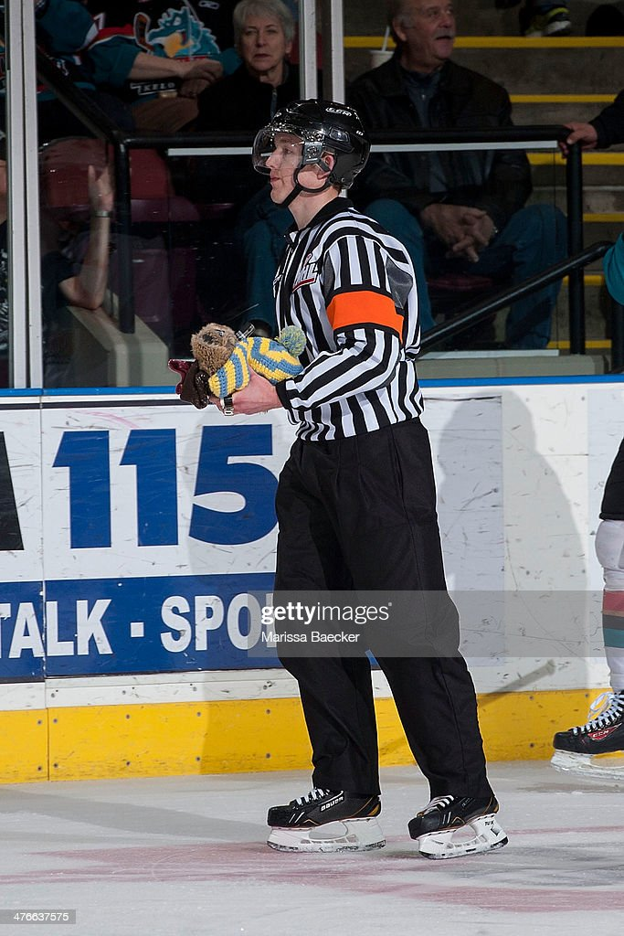 A referee takes several hats to the officials box after Tyrell Goulbourne #12 of the Kelowna Rockets scored his third goal and fans celebrated the hat trick against the Prince George Cougars on February 25, 2014 at Prospera Place in Kelowna, British Columbia, Canada.