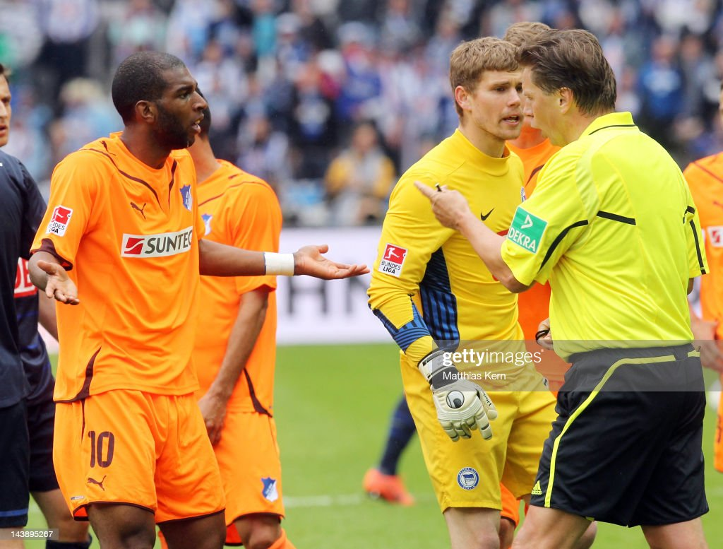 Referee <a gi-track='captionPersonalityLinkClicked' href=/galleries/search?phrase=Thorsten+Kinhoefer&family=editorial&specificpeople=729377 ng-click='$event.stopPropagation()'>Thorsten Kinhoefer</a> (R) talks with <a gi-track='captionPersonalityLinkClicked' href=/galleries/search?phrase=Ryan+Babel&family=editorial&specificpeople=543539 ng-click='$event.stopPropagation()'>Ryan Babel</a> (L) of Hoffenheim during the Bundesliga match between Hertha BSC Berlin and TSG 1899 Hoffenheim at Olympic Stadium on May 5, 2012 in Berlin, Germany.