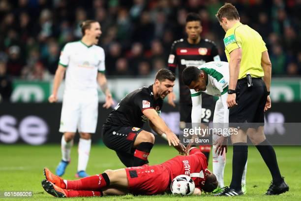 Referee Tobias Stieler Aleksandar Dragovic of Leverkusen and Theodor Gebre Selassie of Bremen look after goalkeeper Bernd Leno of Leverkusen during...
