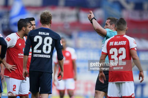 Referee Tobias Stieler calls the Video Assistant Referee during the Bundesliga match between 1 FSV Mainz 05 and Hertha BSC at Opel Arena on September...
