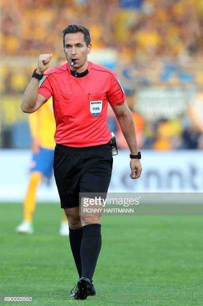 Referee Tobias Stieler gestures during German Bundesliga relegation second leg football match between Eintracht Braunschweig and VfL Wolfsburg on May...