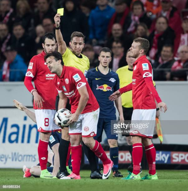 Referee Tobias Stieler gestures shows the yellow card to Giulio Donati of Mainz the Bundesliga match between 1 FSV Mainz 05 and RB Leipzig at Opel...
