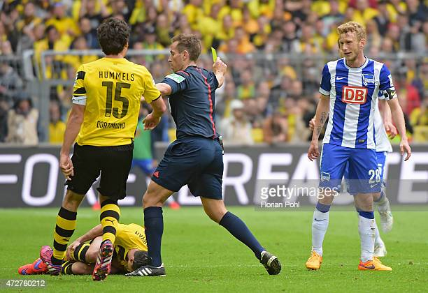 Referee Tobias Stieler mediates the fight between Mats Hummels of Borussia Dortmund and Fabian Lustenberger of Hertha BSC during the game between...