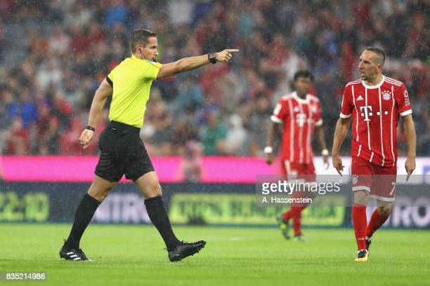 Referee Tobias Stieler points penalty after contacting the videoa referee during the halftime break of the Bundesliga match between FC Bayern...