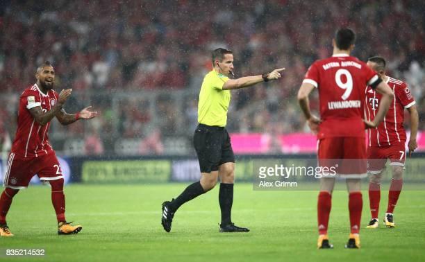 Referee Tobias Stieler points to the penally spot following video proof while Arturo Vidal Franck Ribery oand Robert Lewandowski of Bayern Muenchen...