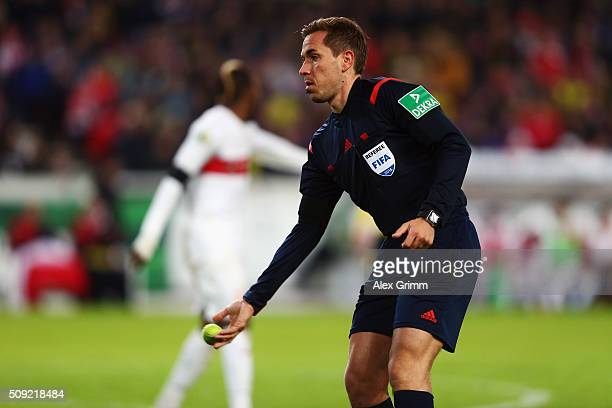 Referee Tobias Stieler removes a tennis ball from the pitch during the DFB Cup Quarter Final match between VfB Stuttgart and Borussia Dortmund at...