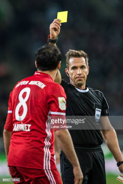 Referee Tobias Stieler show the yellow card to Javi Martinez during the Bundesliga match between Borussia Moenchengladbach and Bayern Muenchen at...