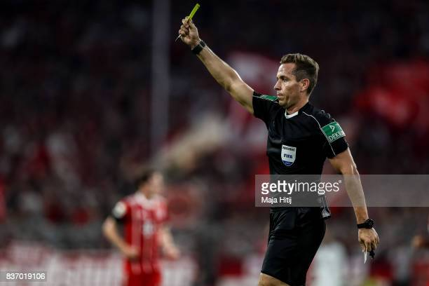 Referee Tobias Stieler shows a yellow card during the Bundesliga match between FC Bayern Muenchen and Bayer 04 Leverkusen at Allianz Arena on August...