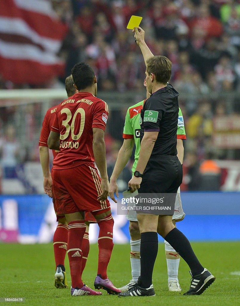 Referee Tobias Stieler (R) shows Bayern Munich's Brazilian midfielder Luiz Gustavo (L) the yellow card during the German first division Bundesliga football match FC Bayern Munich vs Fortuna Duesseldorf, in Munich southern Germany on March 9, 2013.