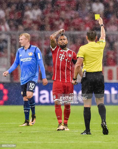 Referee Tobias Stieler shows Bayern Munich's Chilian midfielder Arturo Vidal the yellow card during the German first division Bundesliga football...