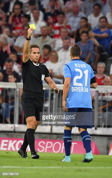 Referee Tobias Stieler shows Dominik Kohr of Bayer Leverkusen a yellow card during the Bundesliga match between FC Bayern Muenchen and Bayer 04...