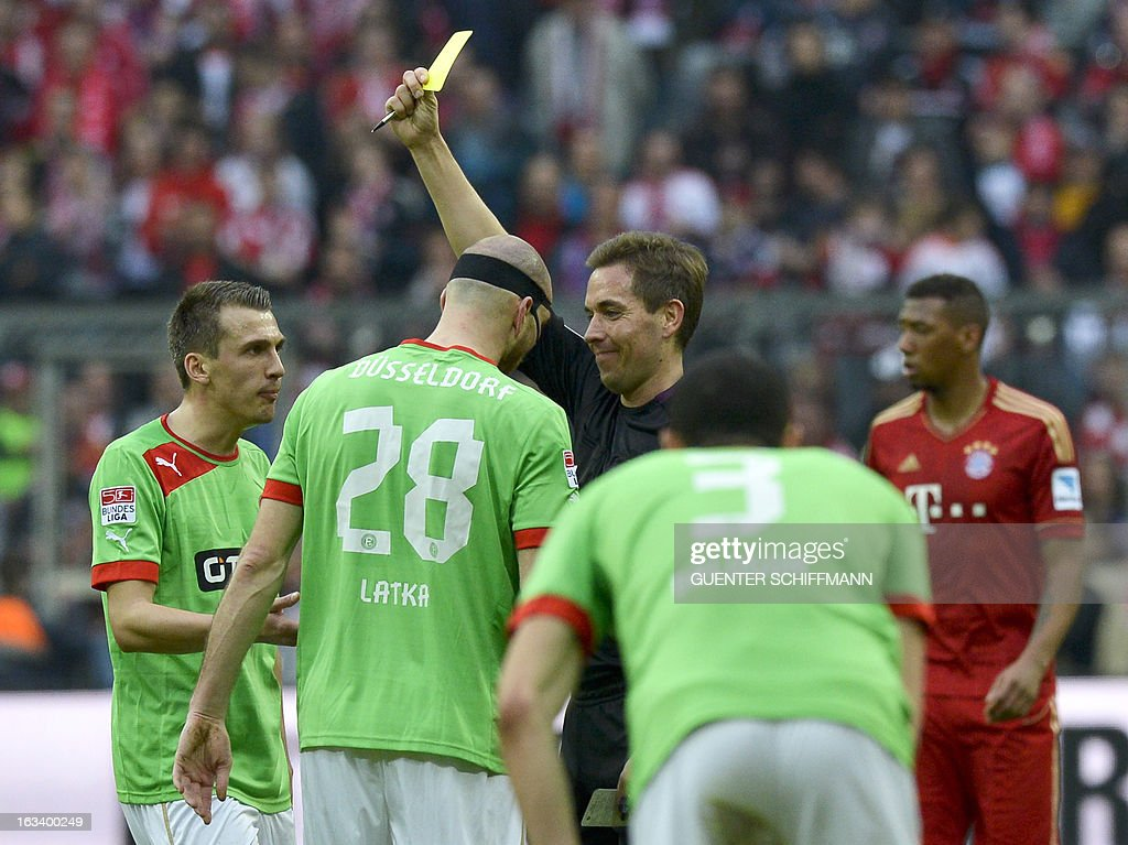 Referee Tobias Stieler (C) shows Duesseldorf's Czech defender Martin Latka (2nd L) the yellow card during the German first division Bundesliga football match FC Bayern Munich vs Fortuna Duesseldorf...