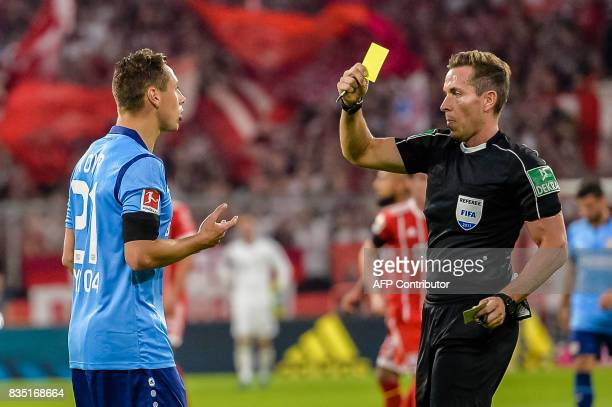 Referee Tobias Stieler shows Leverkusen's midfielder Dominik Kohr the yellow card during the German First division Bundesliga football match FC...