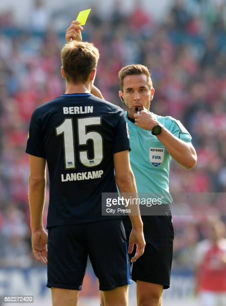 referee Tobias Stieler shows Sebastian Langkamp of Hertha BSC the yellow card during the game between FSV Mainz 05 and Hertha BSC on september 23...