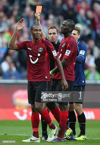 Referee Tobias Stieler shows the red card to Marcelo of Hannover during the Bundesliga match between Hannover 96 and 1899 Hoffenheim at HDI Arena on...
