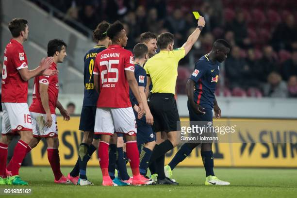 Referee Tobias Stieler shows the yellow card to Dayot Upamecano of Leipzig during the Bundesliga match between 1 FSV Mainz 05 and RB Leipzig at Opel...