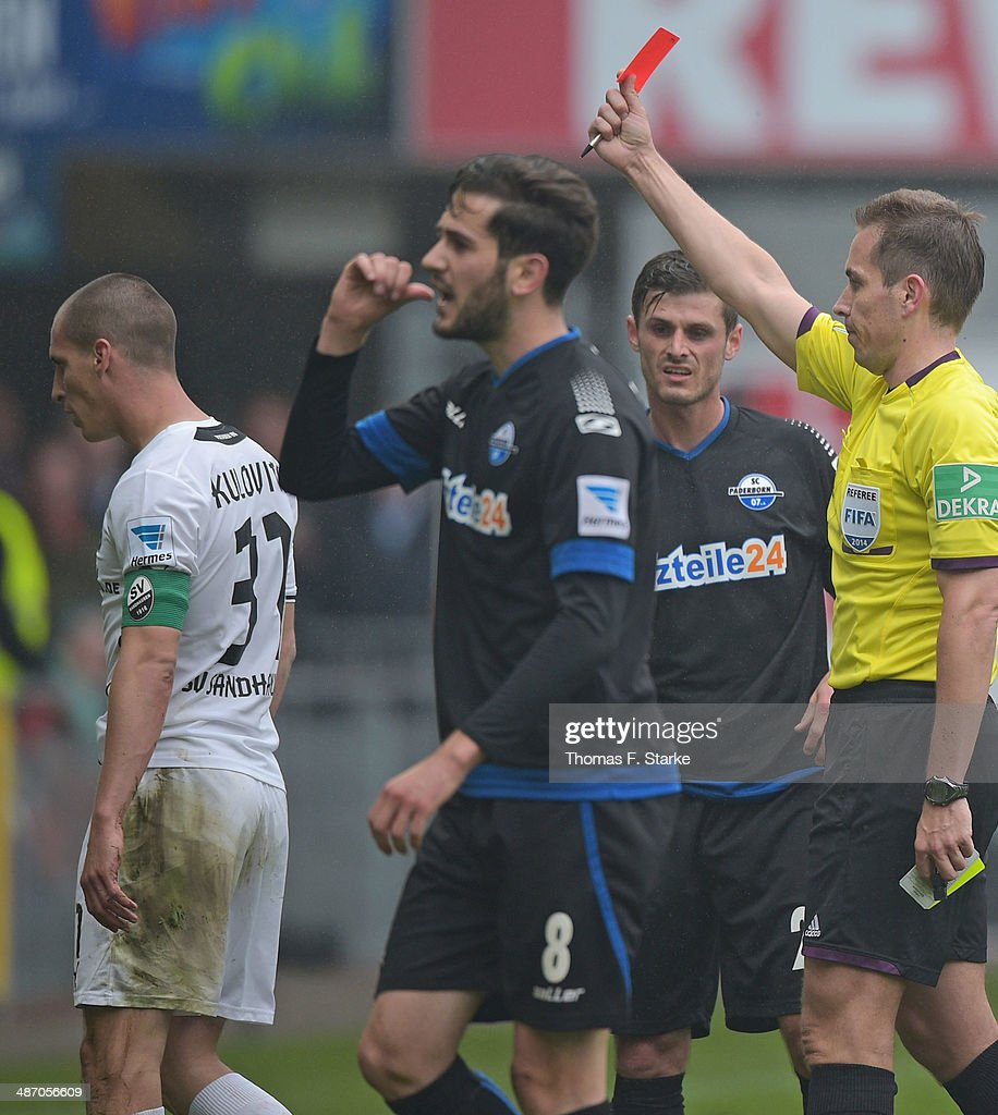 Referee Tobias Stieler (R) shows the yellow red card to Stefan Kulovits (L) of Sandhausen during the Second Bundesliga match between SC Paderborn and SV Sandhausen at Benteler Arena on April 27, 2014 in Paderborn, Germany.