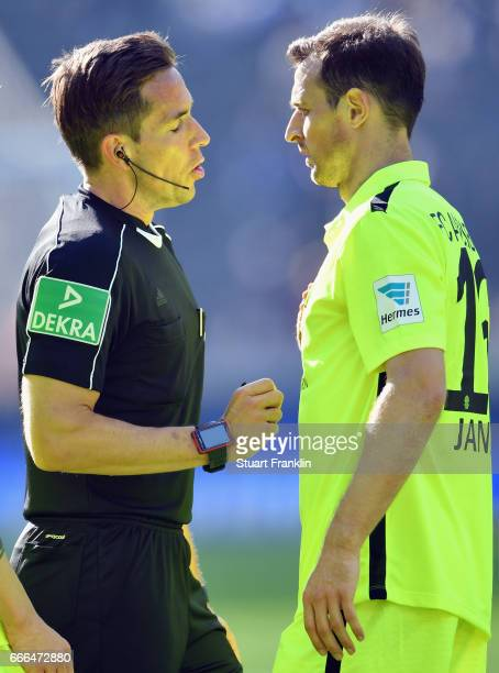Referee Tobias Stieler talks to Christoph Janker of Augsburg during the Bundesliga match between Hertha BSC and FC Augsburg at Olympiastadion on...