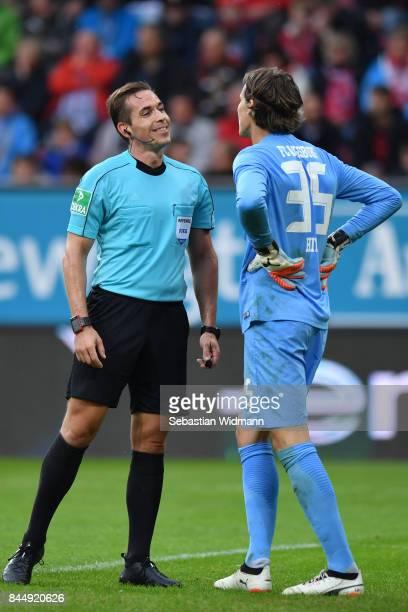 Referee Tobias Stieler talks to Goalkeeper Marwin Hitz of Augsburg during the Bundesliga match between FC Augsburg and 1 FC Koeln at WWKArena on...