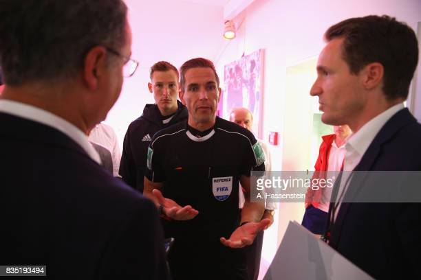 Referee Tobias Stieler talks to officials during the halftime break of the Bundesliga match between FC Bayern Muenchen and Bayer 04 Leverkusen at...