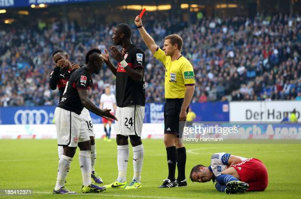 Referee Tobias Welz shows the red card to Antonio Ruediger of Stuttgart next to Rafael van der Vaart of Hamburg during the Bundesliga match between...