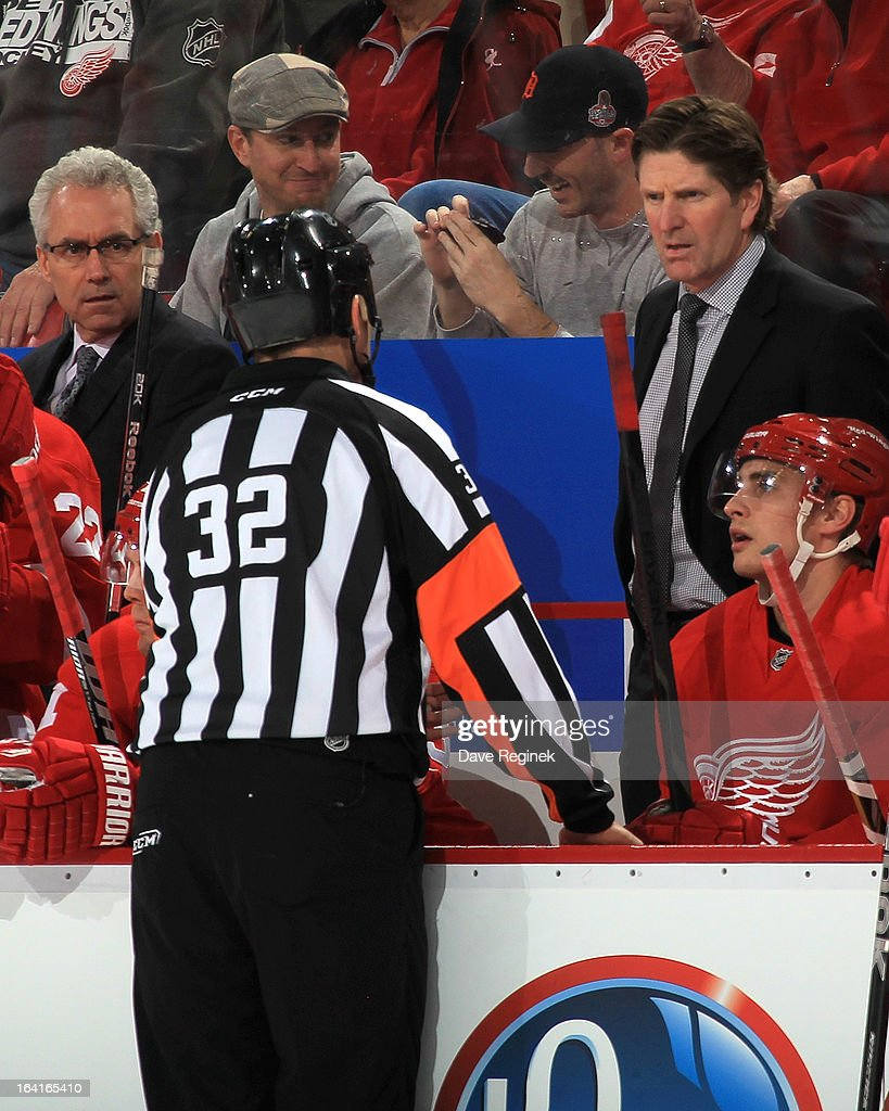 Referee Tom Kowal #32 explains to Mike Babcock head coach of the Detroit Red Wings why a first period goal was called off during a NHL game against the Minnesota Wild at Joe Louis Arena on March 20, 2013 in Detroit, Michigan.