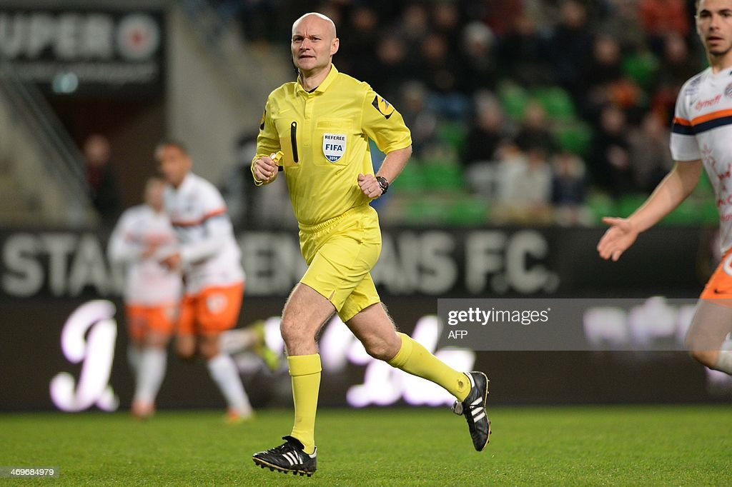 Referee Tony Chapron runs during the French L1 football match between Rennes and Montpellier on February 15, 2014 at the Route de Lorient stadium in Rennes, western France.