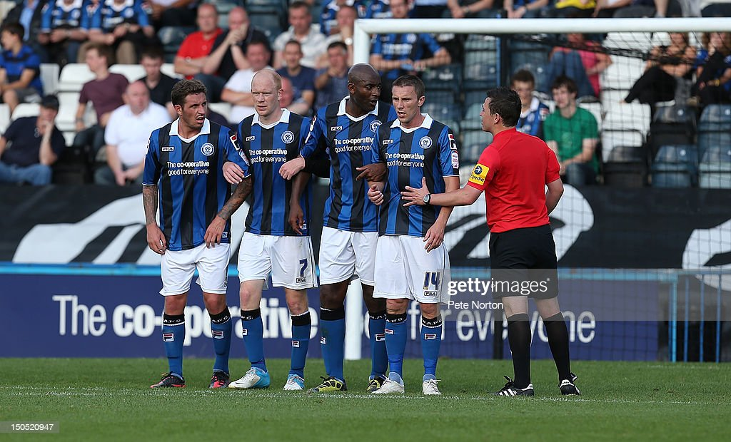 Referee Tony Harrington organises the Rochdale defensive wall of George Donnelly, Jason Kennedy, <a gi-track='captionPersonalityLinkClicked' href=/galleries/search?phrase=Dele+Adebola&family=editorial&specificpeople=792731 ng-click='$event.stopPropagation()'>Dele Adebola</a> and Kevin McIntyre during the npower League Two match between Rochdale and Northampton Town at Spotland Stadium on August 18, 2012 in Rochdale, England.