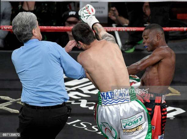 Referee Vik Drakulich steps in at the end of the first round of the super bantamweight championship bout between Moises Flores and Guillermo...