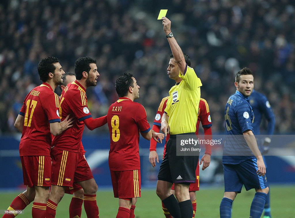 Referee <a gi-track='captionPersonalityLinkClicked' href=/galleries/search?phrase=Viktor+Kassai&family=editorial&specificpeople=3084826 ng-click='$event.stopPropagation()'>Viktor Kassai</a> gives a yellow card to Xavi Hernandez of Spain during the FIFA World Cup 2014 qualifier match between France and Spain at the Stade de France on March 26, 2013 in Saint-Denis near Paris, France.