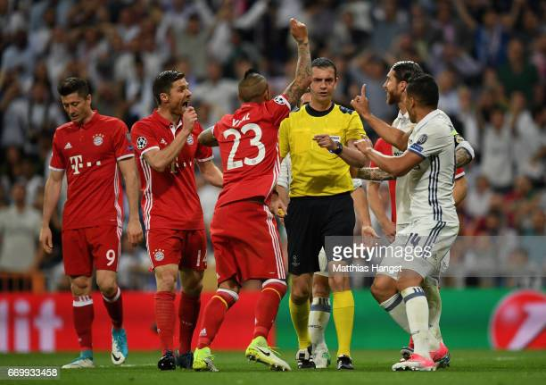 Referee Viktor Kassai is surrounded by Arturo Vidal of Bayern Muenchen as he appeals for a penalty as Casemiro of Real Madrid argues during the UEFA...