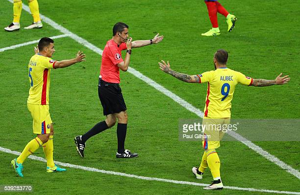 Referee Viktor Kassai points the penalty spot after Patrice Evra of France fouling Nicolae Stanciu of Romania in the area during the UEFA Euro 2016...