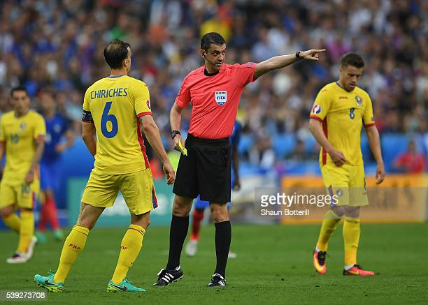 Referee Viktor Kassai prepares for an yellow card to Vlad Chiriches during the UEFA Euro 2016 Group A match between France and Romania at Stade de...