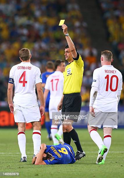 Referee Viktor Kassai show Steven Gerrard of England a yellow card during the UEFA EURO 2012 group D match between England and Ukraine at Donbass...