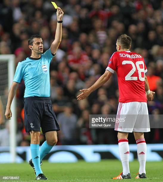 Referee Viktor Kassai shows a yellow card to Morgan Schneiderlin of Manchester United during the Champions League match between Manchester United and...