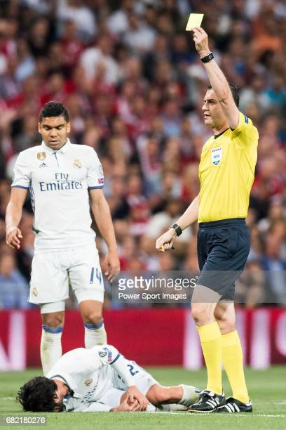Referee Viktor Kassai shows a yellow card to Xabi Alonso of FC Bayern Munich as Isco Alarcon of Real Madrid lies on the pitch injured during their...