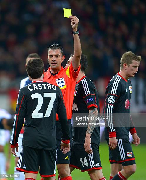Referee Viktor Kassai shows Gonzalo Castro of Bayer Leverkusen a yellow card during the UEFA Champions League Round of 16 first leg match between...