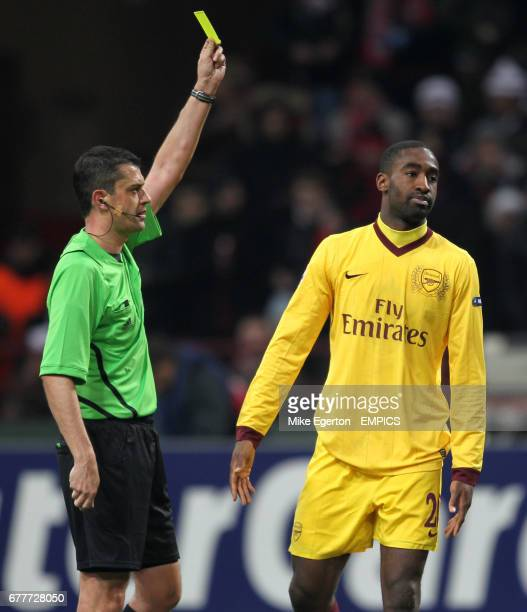 Referee Viktor Kassai shows the yellow card to Arsenal's Johan Djourou
