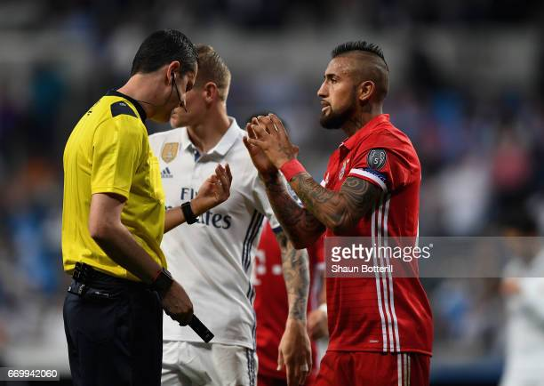Referee Viktor Kassai speaks to Arturo Vidal of Bayern Muenchen during the UEFA Champions League Quarter Final second leg match between Real Madrid...