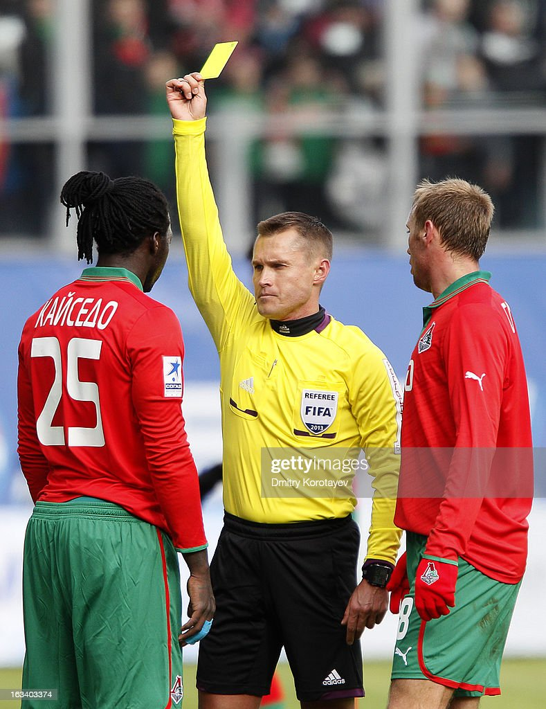 Referee Vladislav Bezborodov shows a yellow card to Felipe Caicedo of FC Lokomotiv Moscow during the Russian Premier League match between Dinamo Moskva and FC Lokomotiv Moscow at the Arena Khimki Stadium on March 09, 2013 in Khimki, Russia.