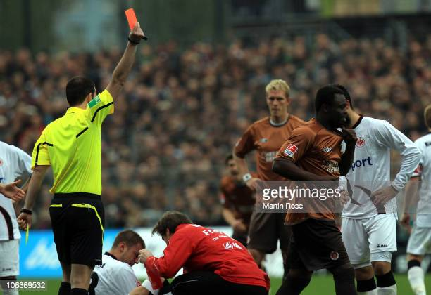 Referee Volker Wenzel shows Gerald Asamoah of St Pauli the yellow red card during the Bundesliga match between FC St Pauli and Eintracht Frankfurt at...