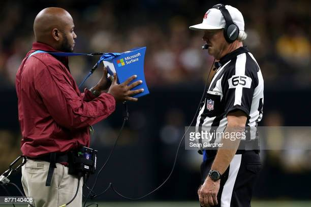 Referee Walt Coleman looks at a Instant Replay on a Microsoft Surface during between the New Orleans Saints and the Washington Redskins NFL game at...
