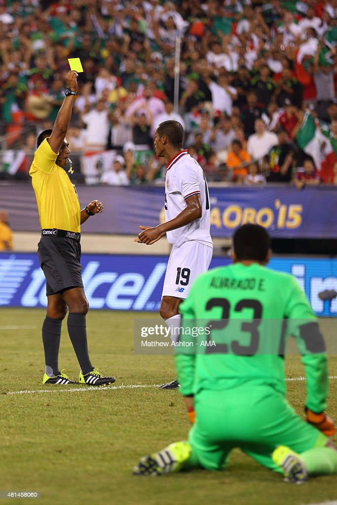 Referee Walter Lopez awards Roy Miller of Costa Rica a yellow card after his foul on Oribe Peralta of Mexico which resulted in a penalty and the winning goal during the Gold Cup Quarter Final between Mexico and Costa Rica at MetLife Stadium on July 19, 2015 in East Rutherford, New Jersey.
