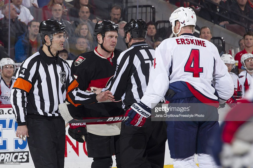 Referee Wes McCauley #4 and linesman Michel Cormier #76 separate Chris Neil #25 of the Ottawa Senators and John Erskine #4 of the Washington Capitals during an NHL game at Scotiabank Place on January 29, 2013 in Ottawa, Ontario, Canada.
