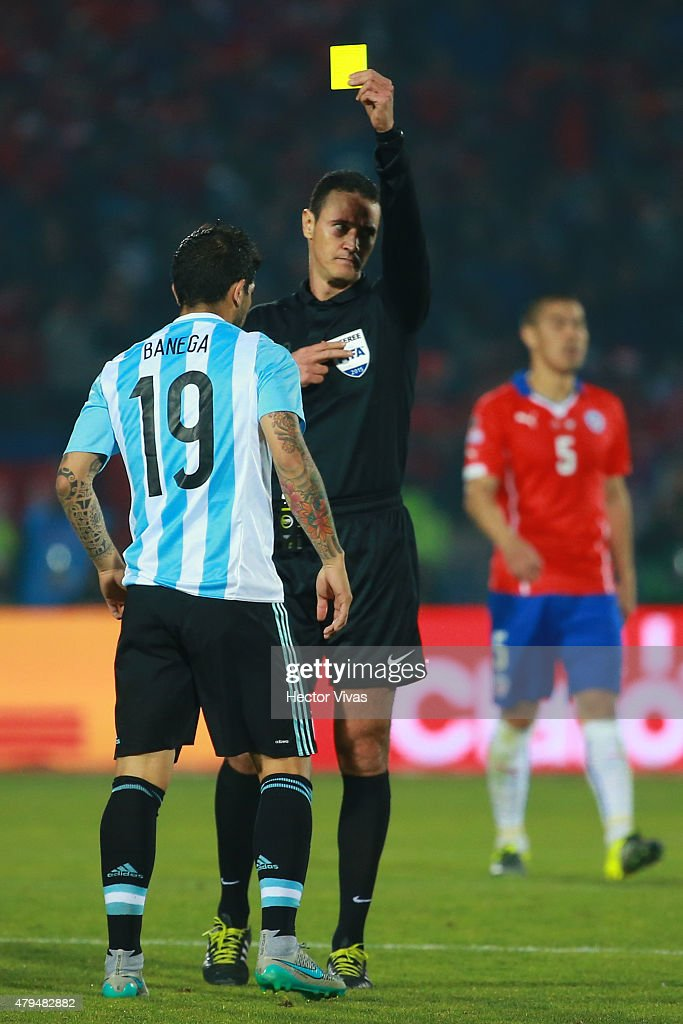 Referee Wilmar Roldan shows a yellow card to <a gi-track='captionPersonalityLinkClicked' href=/galleries/search?phrase=Ever+Banega&family=editorial&specificpeople=4100796 ng-click='$event.stopPropagation()'>Ever Banega</a> of Argentina during the 2015 Copa America Chile Final match between Chile and Argentina at Nacional Stadium on July 04, 2015 in Santiago, Chile.