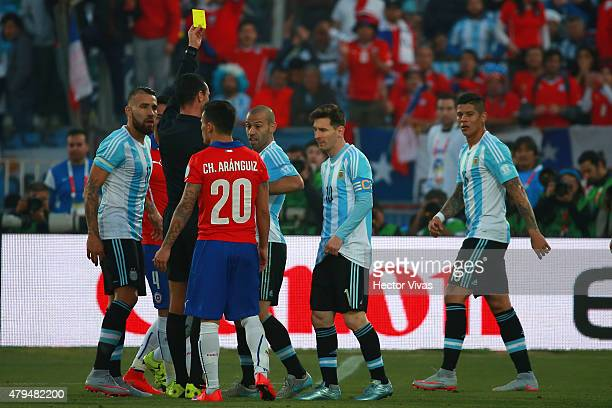Referee Wilmar Roldan shows a yellow card to Javier Mascherano of Argentina during the 2015 Copa America Chile Final match between Chile and...