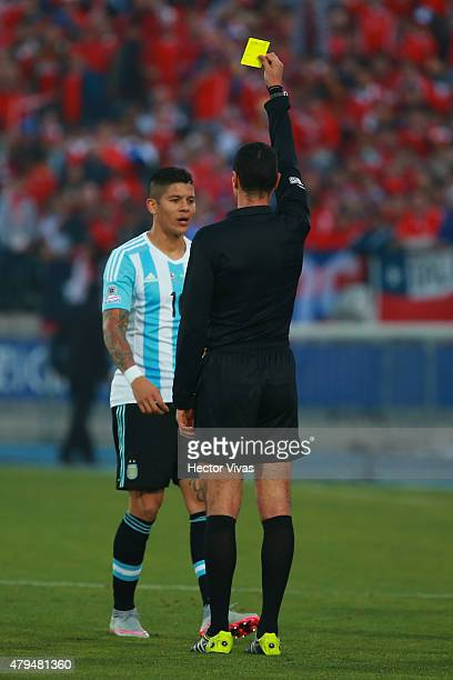 Referee Wilmar Roldan shows a yellow card to Marcos Rojo of Argentina during the 2015 Copa America Chile Final match between Chile and Argentina at...