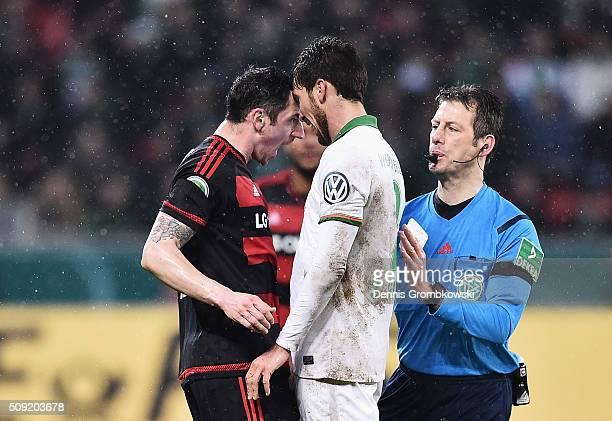 Referee Wolfgang Stark intervenes as Roberto Hilbert of Bayer Leverkusen and Santiago Garcia of Werder Bremen clash during the DFB Cup Quarter Final...