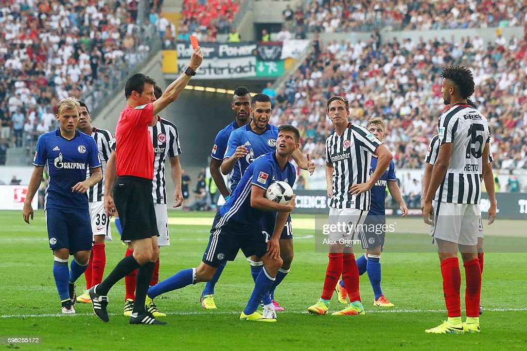 Referee Wolfgang Stark shows the red card to Michael Hector (R) of Frankfurt during the Bundesliga match between Eintracht Frankfurt and FC Schalke 04 at Commerzbank-Arena on August 27, 2016 in Frankfurt am Main, Germany.